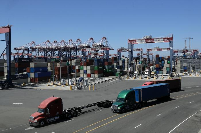 In this Aug. 22, 2018, file photo, trucks travel along a loading dock at the Port of Long Beach in Long Beach, Calif.