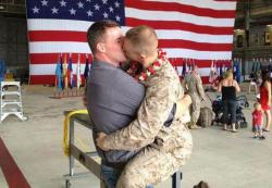 Sgt. Brandon Morgan and his partner Dalan Wells sharing a welcome home kiss in Hawaii in 2012