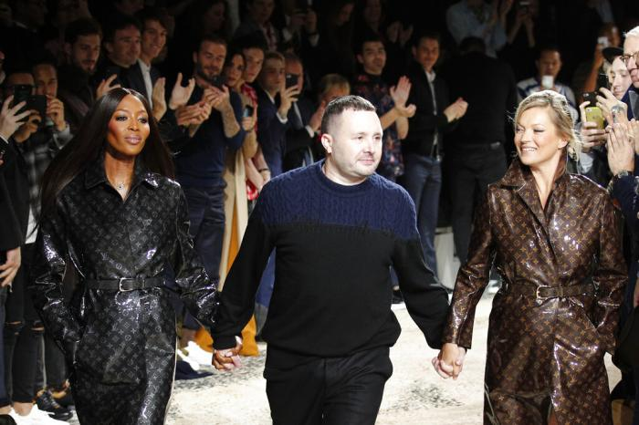 Designer Kim Jones, center, accepts applause as he walks with models Kate Moss, right, and Naomi Campbell after his Louis Vuitton men's Fall-Winter 2018/2019 fashion collection.