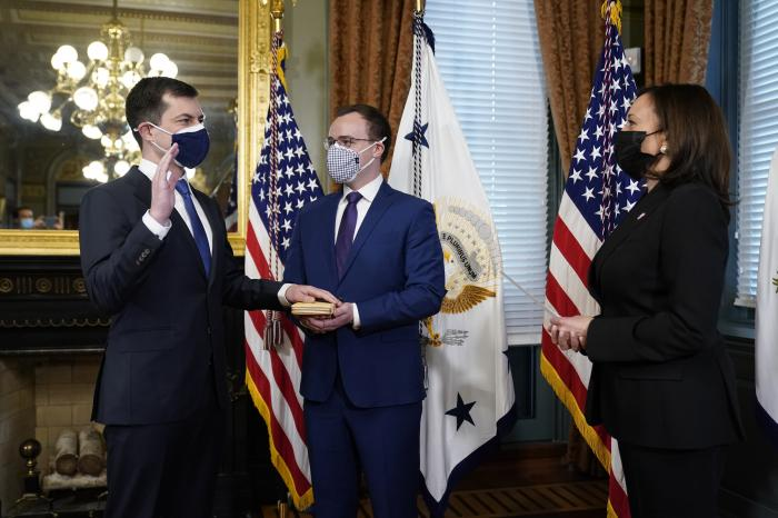 Pete Buttigieg, with his hand on the Bible held by Chasten Buttigieg, is sworn in as Transportation Secretary by Vice President Kamala Harris in the Old Executive Office Building in the White House complex in Washington.