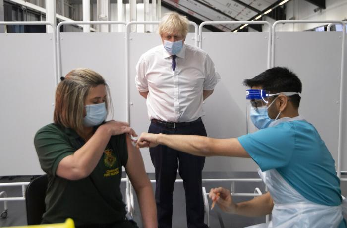 Britain's Prime Minister Boris Johnson watches first responder Caroline Cook receiving an injection of a Covid-19 vaccine at Ashton Gate Stadium in Bristol, England.
