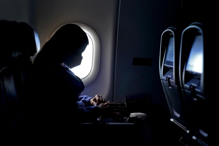 A passenger wears a face mask she travels after take off from Hartsfield-Jackson International Airport in Atlanta.