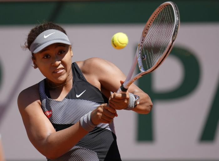 Japan's Naomi Osaka returns the ball to Romania's Patricia Maria Tig during their first round match of the French open tennis tournament at the Roland Garros stadium.