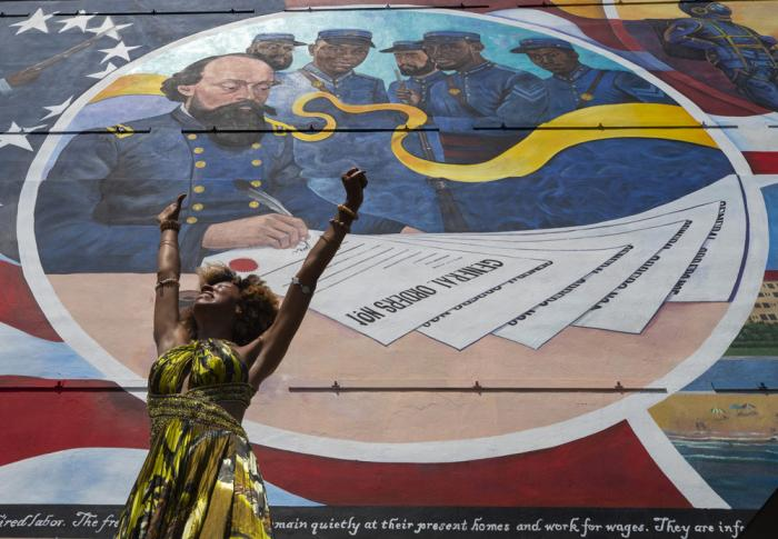 """Dancer Prescylia Mae, of Houston, performs during a dedication ceremony for the massive mural """"Absolute Equality"""" in downtown Galveston, Texas, Saturday, June 19, 2021"""