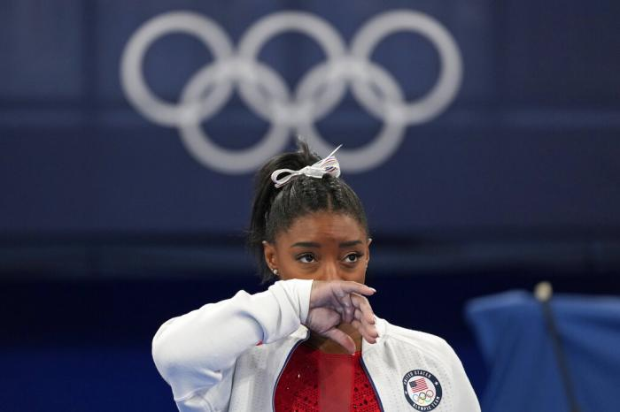 Simone Biles, of the United States, watches gymnasts perform at the 2020 Summer Olympics.